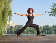 Mature woman standing in the morning sun practicing yoga outdoor
