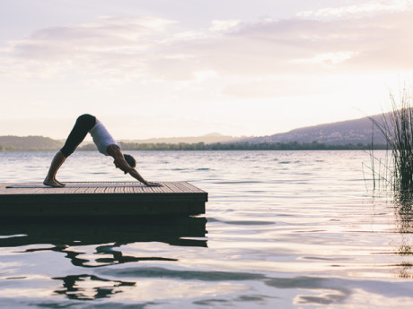 Woman doing yoga in the nature at sunset.